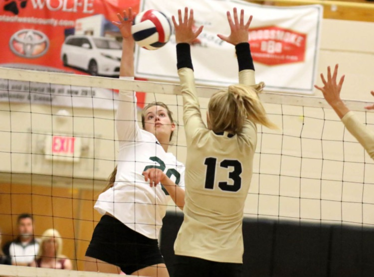 Morgan Smith takes a huge jump to hit the volleyball.