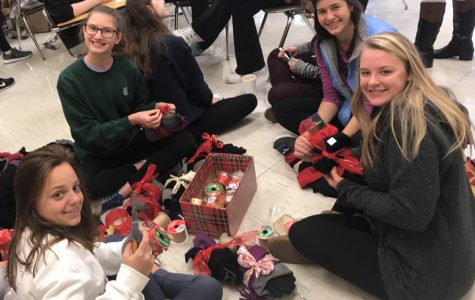 Students from all grades including Kristin Strout (junior), Chickie Slane (senior), Molly Boersig (senior), Olivia Sullivan (sophomore) and Sara Frautschi (freshman) gathered in Mrs. Jane Garvin's classroom to sort hats, gloves, and scarves to be wrapped with Christmas ribbon and distributed to our dear neighbors at Saints Peter and Paul.