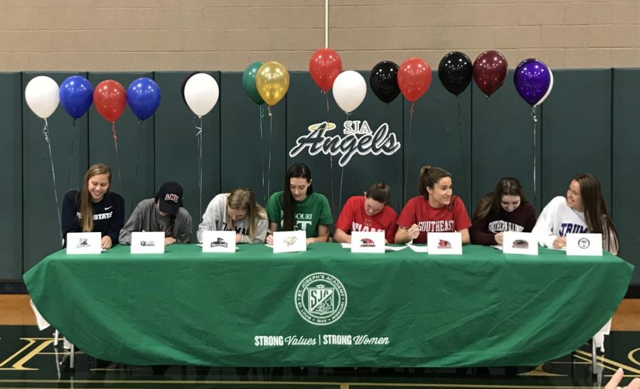 Gabby Blossom, Emily Ferbet, Madison Gresham, Alex Kerr, Annie Kreikemeier, Claire Ochs, Grace Renfer, and Morgan Smith signing their letters.