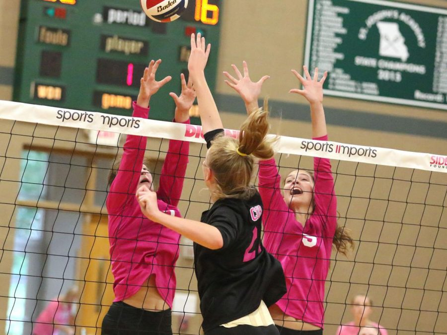 Photo courtesy of Paul Kopsky.  Gabbie Noonan and Amanda Meyer block a ball during the Dig Pink game.
