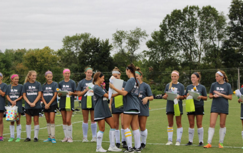 Lily Johnston, Annie Hoffmeister, and Laura Halliday present senior, Joni Halliday, with gifts during the Field Hockey Senior Night.