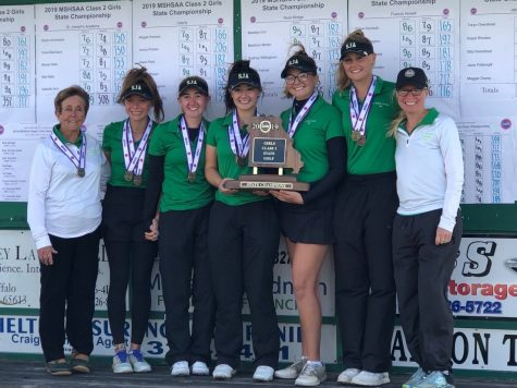 The golf team poses with their fourth consecutive state trophy.