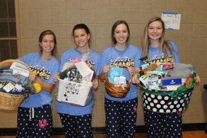 Last year's sophomore class officers sport their Mission Week gear and holding their raffle baskets.