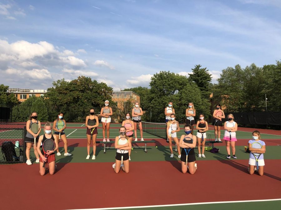 The JV tennis team, socially distanced with masks on, ready to practice for the day.