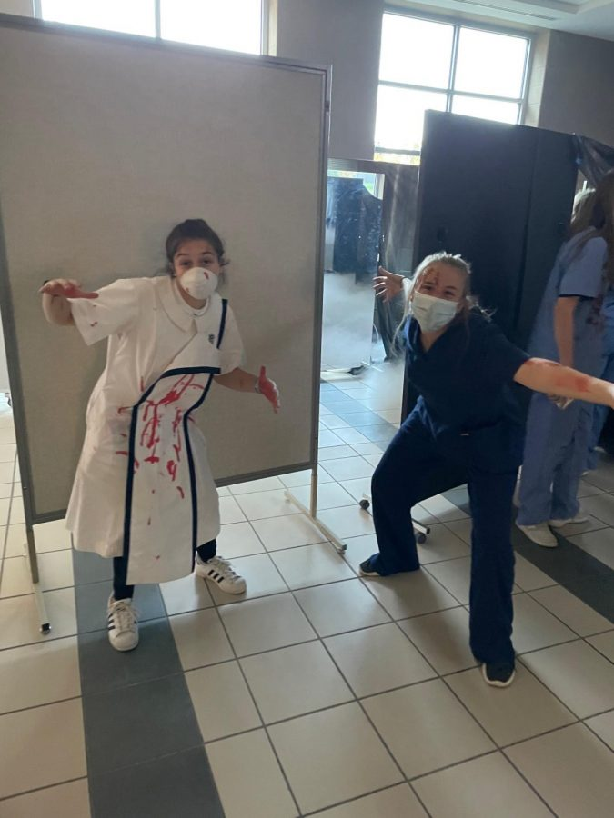 Seniors Caroline Mentel and Lizzie Hickman prepare to scare at senior haunted hallway.