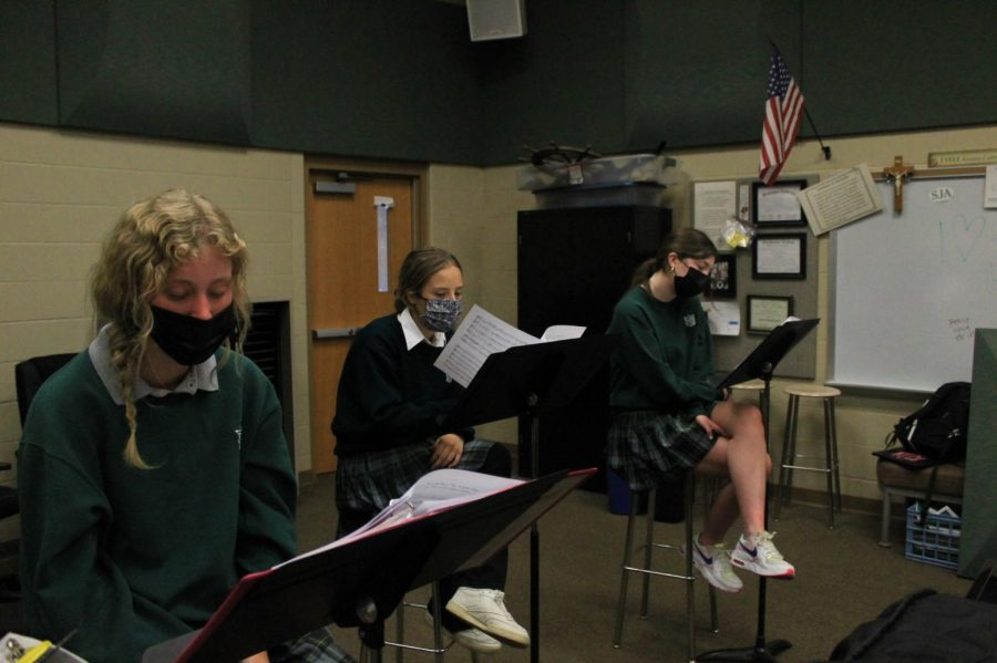 Sophomore Meredith Dunn, junior Kate Theerman-Rodriguez, and senior Kathleen Dolan practice for the upcoming Winter Concert.